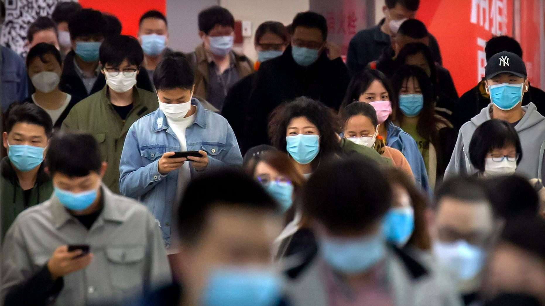 """Commuters wear face masks to protect against the spread of new coronavirus as they walk through a subway station in Beijing, Thursday, April 9, 2020. China's National Health Commission on Thursday reported dozens of new COVID-19 cases, including most of which it says are imported infections in recent arrivals from abroad and two """"native"""" cases in the southern province of Guangdong. (AP Photo/Mark Schiefelbein)"""