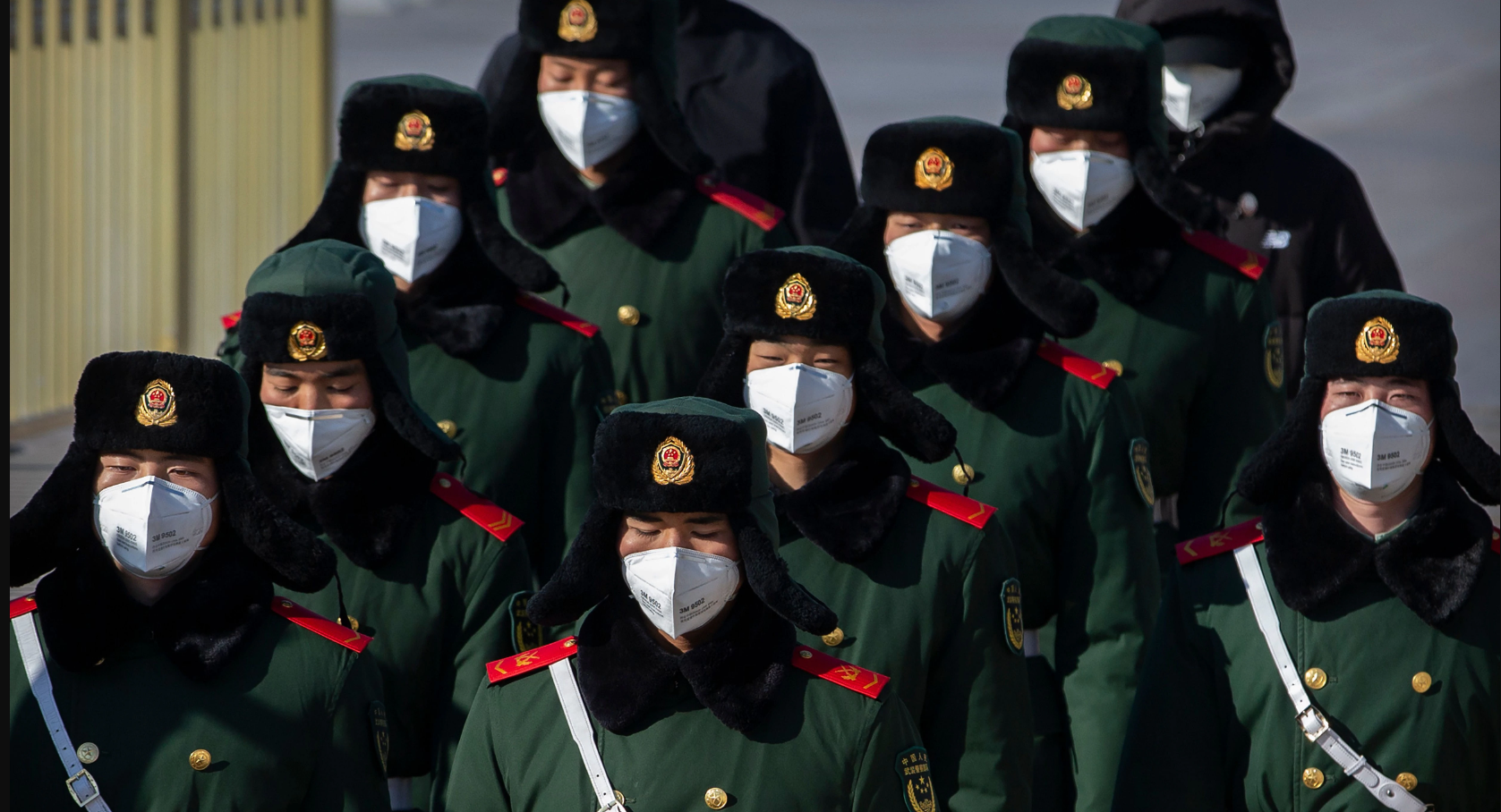 Paramilitary policemen wear face masks as they march in formation near Tiananmen Square in Beijing on February 4. Credit: Mark Schiefelbein/AP