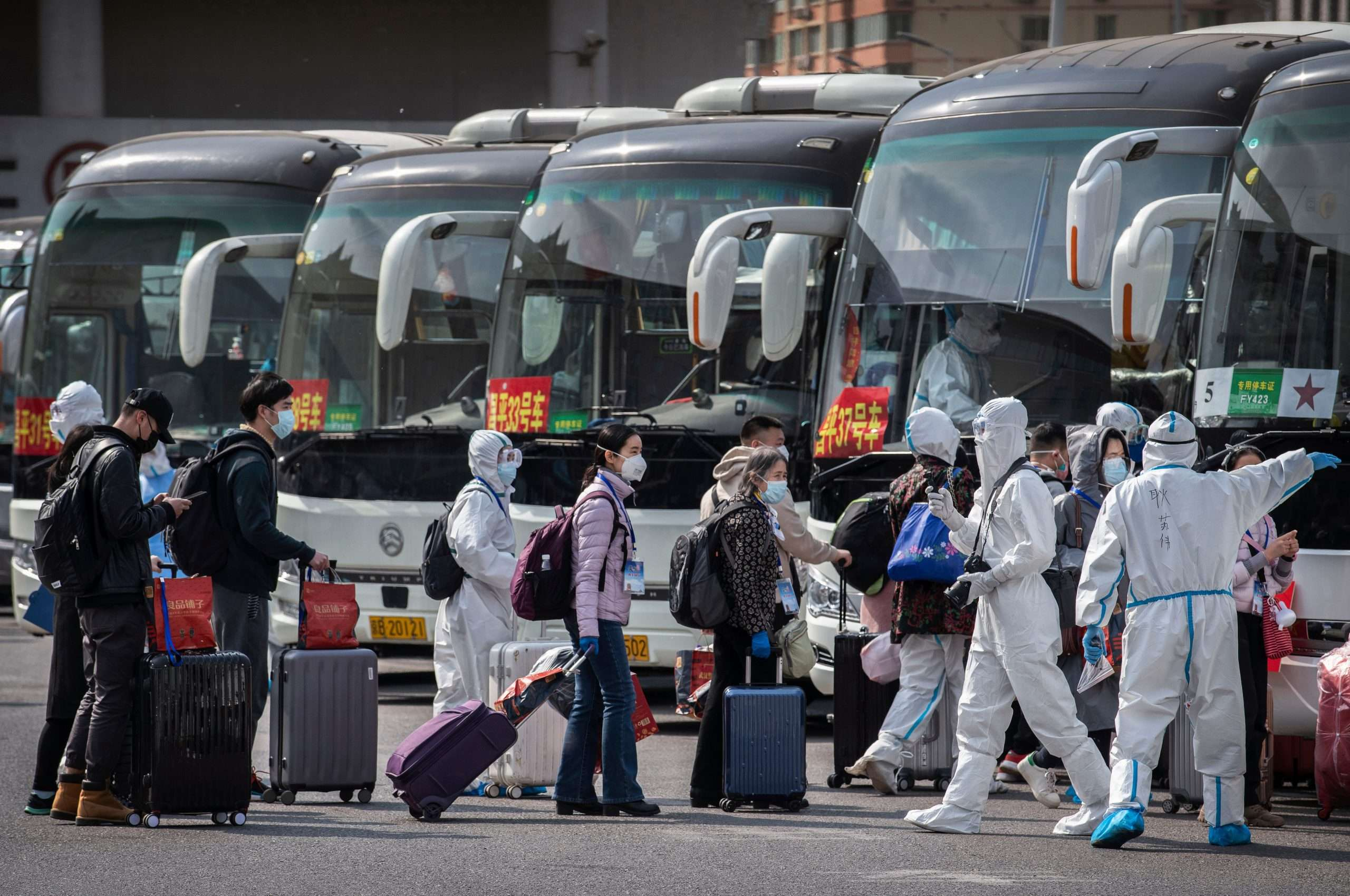 Chinese workers and health officials wear protective suits as travellers from Wuhan are processed after the central Chinese city lifted its lockdown on Wednesday. Credit: Kevin Frayer/Getty