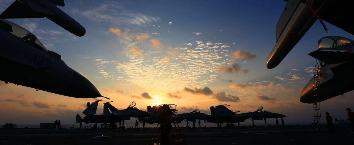 People's Liberation Army Navy J-15 fighter jets are silhouetted on the flight deck of China's aircraft carrier, The Liaoning, during a naval exercise in the western Pacific, April 21, 2018.