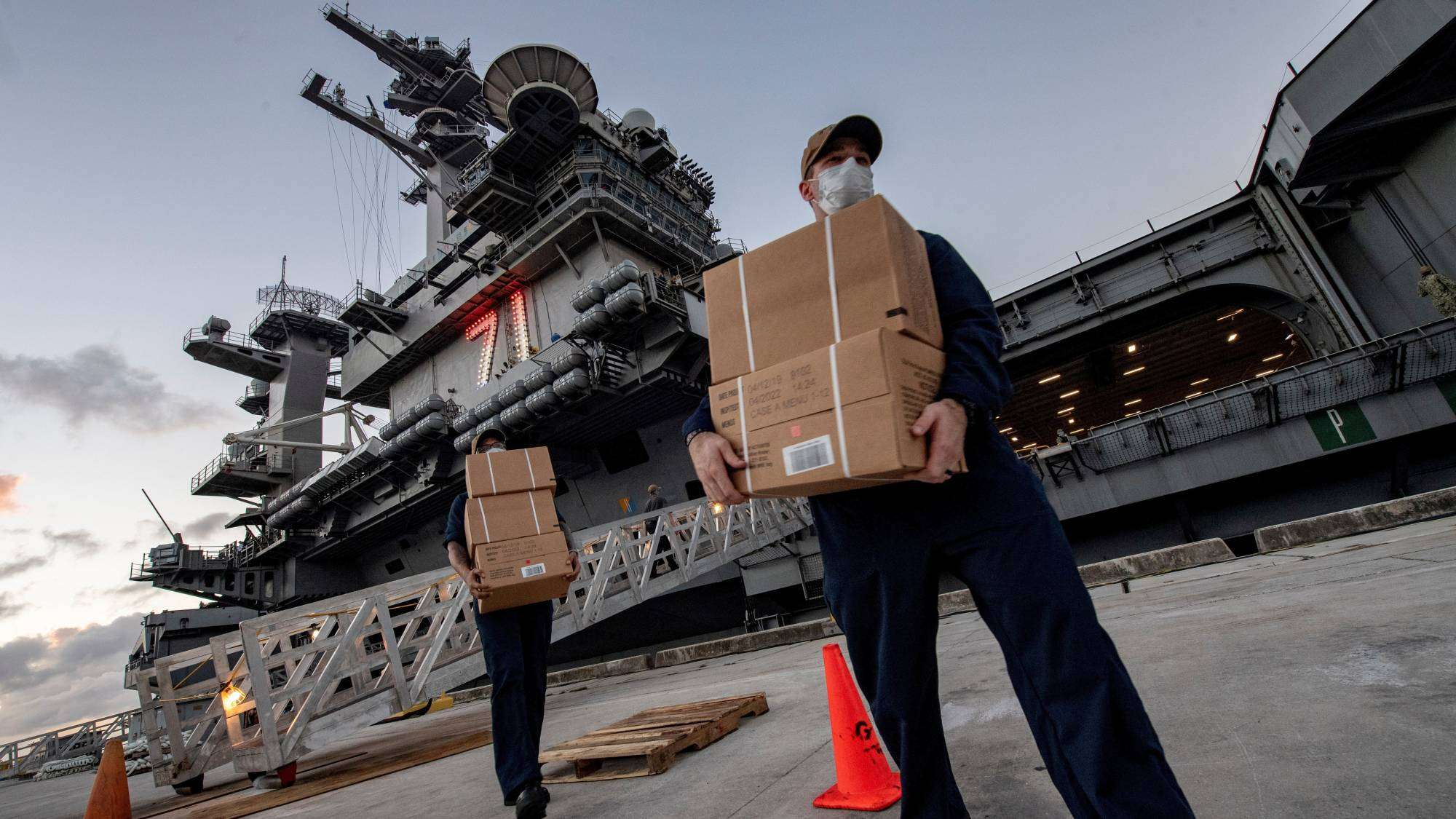 U.S. Navy sailors assigned to the aircraft carrier USS Theodore Roosevelt move meals ready to eat (MREs) for sailors who have tested negative for the new coronavirus and are asymptomatic while quarantined at local hotels in an effort to implement social distancing at the naval base on the Pacific island of Guam on April 7.
