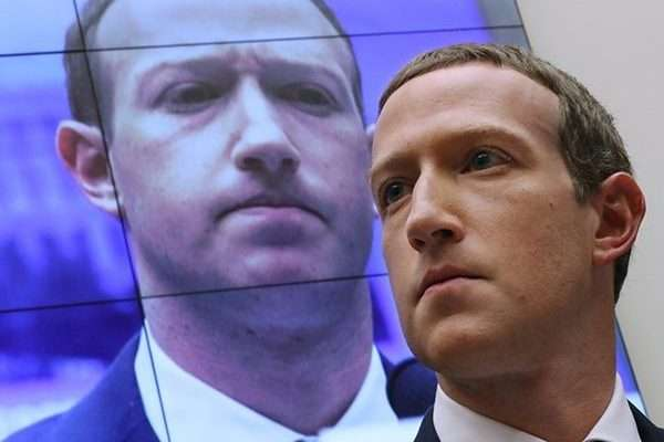 WASHINGTON, DC - OCTOBER 23: With an image of himself on a screen in the background, Facebook co-founder and CEO Mark Zuckerberg testifies before the House Financial Services Committee in the Rayburn House Office Building on Capitol Hill October 23, 2019 in Washington, DC. Zuckerberg testified about Facebook's proposed cryptocurrency …