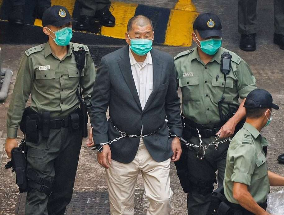 Pro-democracy businessman Jimmy Lai, chained round his waist and wrists to a guard, is marched to court yesterday 12 Dec 2020 Hong Kong